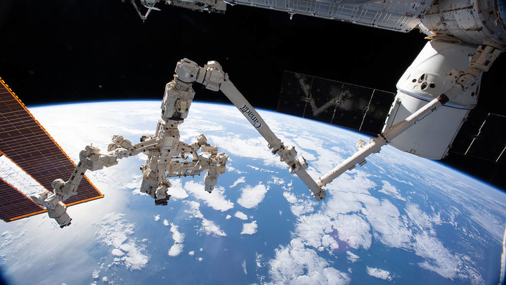 The Canadarm2 robotic arm with its robotic hand, also known as Dextre, attached for fine-tuned robotics work extends across the frame on the International Space Station. NASA sought plans from a dozen companies to launch a commercial low earth orbit space station.