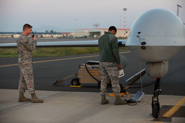 Airmen attached to the 324th Expeditionary Reconnaissance Squadron perform a preflight inspection on an MQ-1 Predator unmanned aerial vehicle.