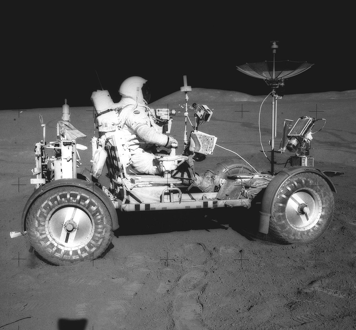 This photograph was taken during the Apollo 15 mission on the lunar surface. Astronaut David R. Scott waits in the Lunar Roving Vehicle (LRV) for astronaut James Irwin for the return trip to the Lunar Module, Falcon, with rocks and soil collected near the Hadley-Apernine landing site. The Apollo 15 was the first mission to use the LRV. Powered by battery, the lightweight electric car greatly increased the range of mobility and productivity on the scientific traverses for astronauts. It weighed 462 pounds (77 pounds on the Moon) and could carry two suited astronauts, their gear and cameras, and several hundred pounds of bagged samples. The LRV's mobility was quite high. It could climb and descend slopes of about 25 degrees. The LRV was designed and developed by the Marshall Space Flight Center and built by the Boeing Company.