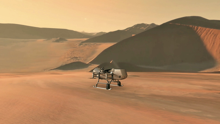 This illustration shows NASA's Dragonfly rotorcraft-lander approaching a site on Saturn's exotic moon, Titan. Taking advantage of Titan's dense atmosphere and low gravity, Dragonfly will explore dozens of locations across the icy world, sampling and measuring the compositions of Titan's organic surface materials to characterize the habitability of Titan's environment and investigate the progression of prebiotic chemistry.