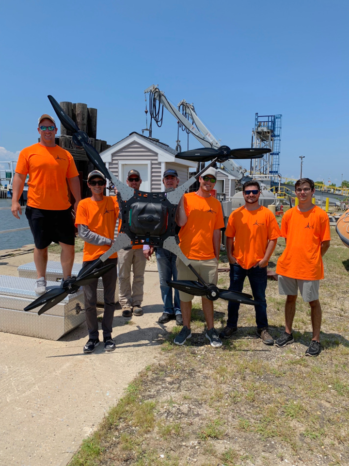 The AATI flight crew pictured with the UAS used during the mission. The custom-built aircraft is roughly 10 feet across in length.